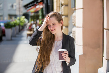 Young beautiful business woman standing on the street with coffee and smart phone. Smiling and talking on the phone.