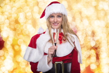 Beautiful young girl in a Christmas costume. New Year's holidays. Woman celebrating Christmas. Girl with a glass of champagne