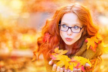 Frau mit Blättern im Herbst