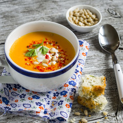 pumpkin soup in white ceramic Cup and a piece of cake with cheese and herbs on a light wooden background