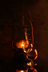 Cognac in glass and cigar on the background of a burning lantern..