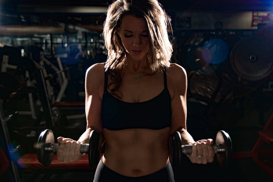 Fit woman doing bicep curl in a gym dramatic light