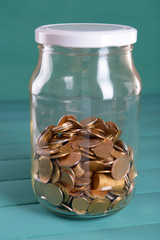 Glass jar with coins on blue background
