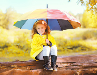Cute little girl child with colorful umbrella in sunny autumn pa