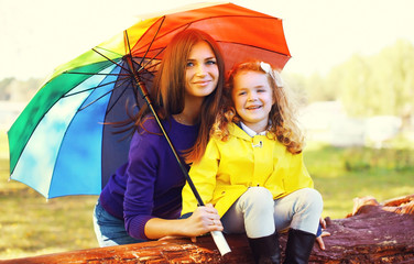 Portrait of happy smiling mother and child with umbrella in autu