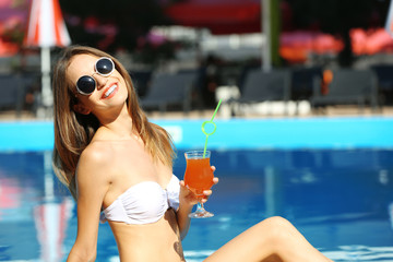 Young woman enjoying with cocktail at swimming pool