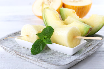 Melon ice lolly on wooden table, closeup