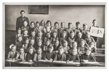 Group of children and teacher in the classroom. Retro picture