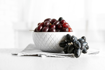 Fresh ripe grapes in bowl on wooden table