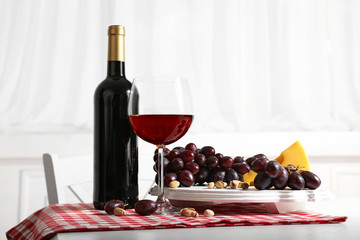 Red grape and cheese with glass bottle of wine on light interior background