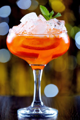 Glass of cocktail with ice on blurred lights background
