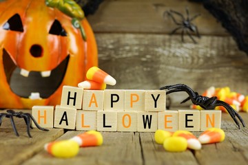 Happy Halloween wooden blocks with candy corn and decor against an old wood background