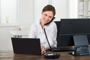 Businesswoman Talking On Phone While Working On Laptop