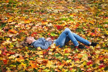 Осень. Осенние листья. Счастливая девушка. Девушка в джинсах лежит на осенних листьях и смотрит в небо. Счастье, отдых, настроение, уикенд