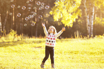 Little girl child enjoying playing with soap bubbles in autumn p