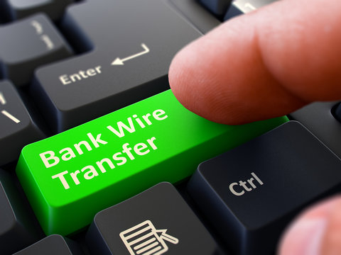 Pressing Green Button Bank Wire Transfer on Black Keyboard.