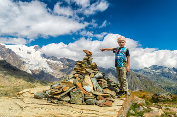Boy pointing out the glacier at Alps, Italy
