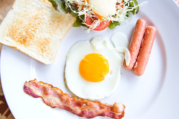 fried eggs with bacon, sausages and toasts on white plate