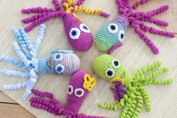 Crocheted woven with colored wool toy octopus close-up, selective focus
