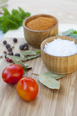 Spices: salt and pepper in wooden pot with tomatoes and herbs close-up, selective focus