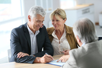 Senior couple meeting real-estate agent for investment