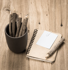 brown notebook and a pencil on wood background,Old style color