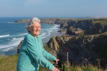 Happy old female pensioner by coast scene Cornwall England UK