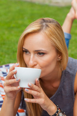 Sensual blonde woman lying in park on blanket. Outdoor photo. She is drinking coffee.