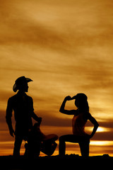 silhouette of a cowgirl kneel on one knee hand on hat
