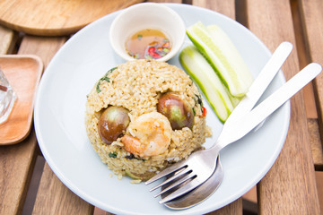 Spicy green curry fired rice with shrimps on wooden table