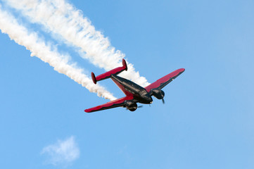 A black and red airplane flying with smoke.