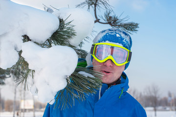 Cheerful snowboarder in sun goggles is standing beside with snow