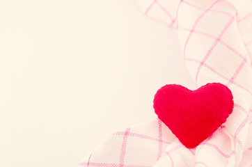 Red heart shape and pink fabric on white background