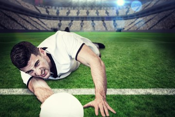 Composite image of man lying down while holding ball