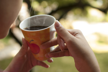 Close-up of person's hand with coffee cup