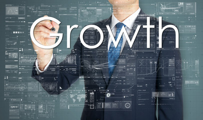 businessman writing growth and drawing graphs and diagrams
