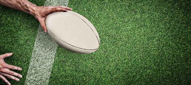 Composite image of cropped image of a man holding rugby ball