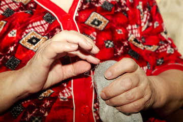 Old woman to sew over a tear