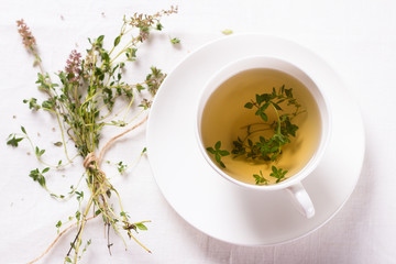 Thyme tea in a white cup on a white napkin. Top view. Selective focus