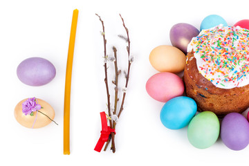 Easter cake, painted eggs and church candle closeup on white background