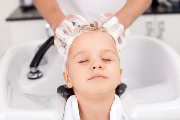 Skilled young hairdresser is treating hair of child