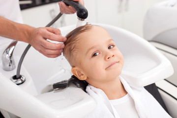Cheerful male child is having hair washed in salon