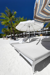 Sun umbrellas and beach beds on tropical coastline