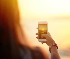 Tourist hand holding smart phone and taking photo of beautiful b