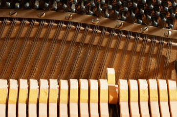 A hammer striking a note inside a piano.