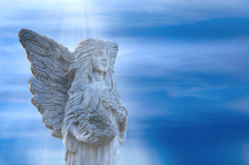 Stone angel statue standing within soft light beams from Heaven with a stormy background. The angel is holding a flower rimmed basket while clutching a rose up to her breast.