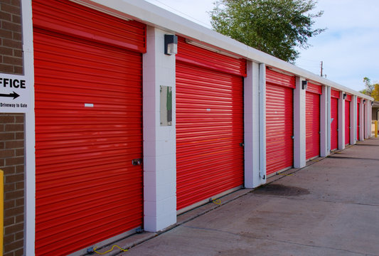 Long row of numbered storage units that are locked with pad locks.