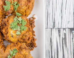 Popular Javanese dish Ayam Penyet or crispy fried chicken in a white plate over wooden background