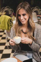 Young blonde woman having a coffee at the city