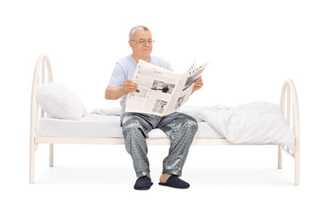 Senior in pajamas reading a newspaper seated on bed